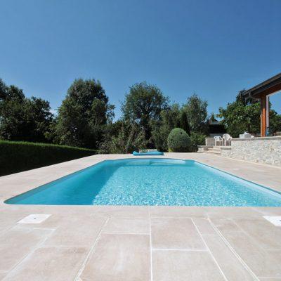Plage de piscine en dalles calcaire beige chez un particulier à Cuvat, 74350