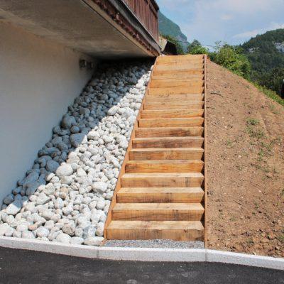 Escalier en poutres chêne et zone de propreté sous balcon en galets granit gris de Chamonix