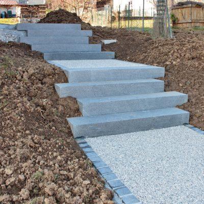 Escalier granit gris foncé avec palier en béton désactivé et ligne de pavés granit gris foncé chez un particulier à Chavanod, 74650