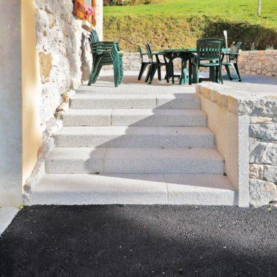 Escalier en blocs de granit gris clair avec un muret à parement de pierres de Grésy. Chez un particulier à Thorens Glières, 74570
