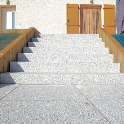 Marches d'escalier en blocs granit gris clair et muret en poutres de chêne